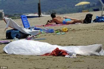 Pengunjung pantai tetap berjemur walau di dekat mereka ada mayat terbungkus plastik